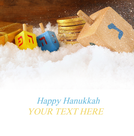 dreidel: image of jewish holiday Hanukkah with wooden colorful dreidels spinning top and chocolate traditional coins over december snow Stock Photo
