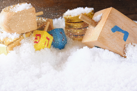 chanukkah: image of jewish holiday Hanukkah with wooden colorful dreidels spinning top and chocolate traditional coins over december snow Stock Photo