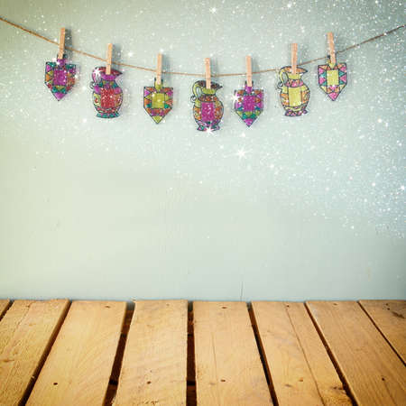 hanukiah: image of jewish holiday Hanukkah with Stained-glass colorful dreidels spinning top hanging on a rope over wooden background. retro filtered image Stock Photo