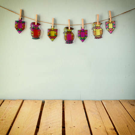 chanukiah: image of jewish holiday Hanukkah with Stained-glass colorful dreidels spinning top hanging on a rope over wooden background. retro filtered image Stock Photo
