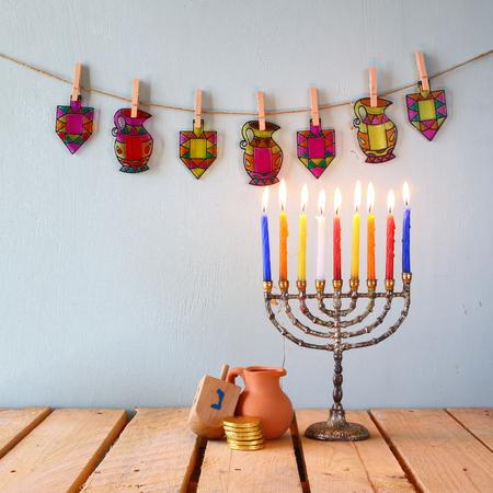 chanukiah: low key image of jewish holiday Hanukkah with menorah traditional Candelabra and wooden dreidels spinning top.