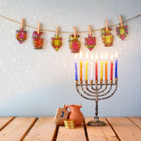 chanukah: low key image of jewish holiday Hanukkah with menorah traditional Candelabra and wooden dreidels spinning top.