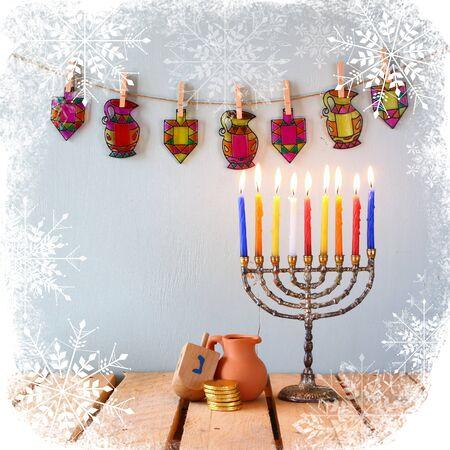 hanoukia: low key image of jewish holiday Hanukkah with menorah traditional Candelabra and wooden dreidels spinning top.
