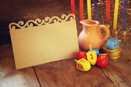 dreidels: image of jewish holiday Hanukkah with menorah traditional Candelabra and wooden dreidels spinning top with empty card for adding text