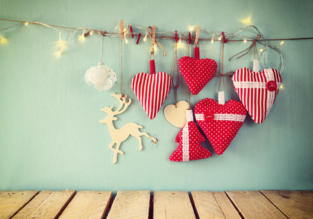 christmas lights background: christmas image of fabric red hearts and garland lights, hanging on rope in front of blue wooden background. retro filtered. Template ready to put photography