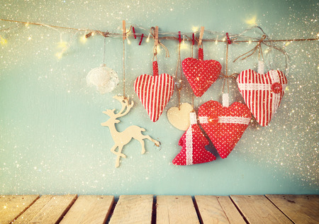 photography background: christmas image of fabric red hearts and garland lights, hanging on rope in front of blue wooden background. retro filtered. Template ready to put photography