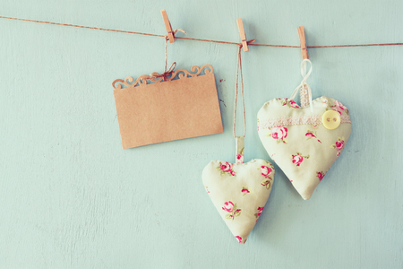filters: christmas image of fabric hearts and empty card for adding text hanging on rope in front of blue wooden background. retro filtered