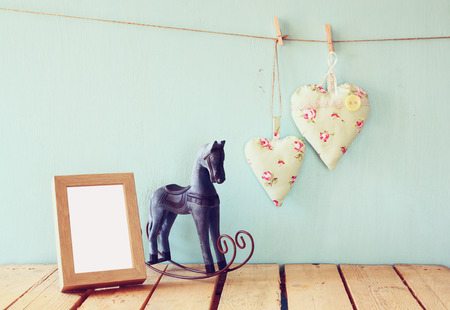kids toys: vintage rocking horse next to fabric hearts hanging on the rope on wooden floor and photo frame. retro filtered image