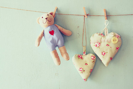 wooden toy: teddy bear and fabric hearts hunging on rope. retro filtered image Stock Photo