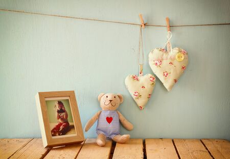 teddy bear background: teddy bear over wood table next to blank photo frame and fabric hearts. retro filtered image Stock Photo