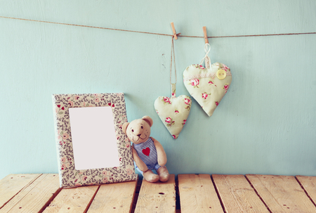 photo frame: teddy bear over wood table next to blank photo frame and fabric hearts. retro filtered image Stock Photo