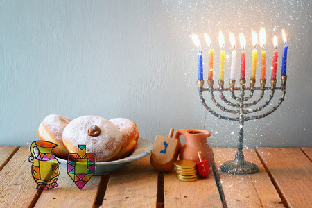 hanukiah: image of jewish holiday Hanukkah with menorah traditional Candelabra, donuts and wooden dreidels spinning top