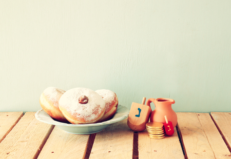 dreidels: image of jewish holiday Hanukkah with donuts and wooden dreidels spinning top. retro filtered