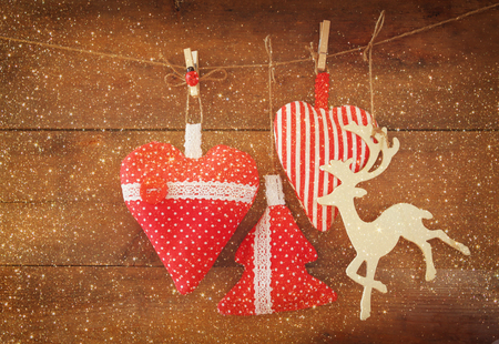 wooden reindeer: Christmas image of fabric red hearts and tree. wooden reindeer and garland lights, hanging on rope in front of wooden background. retro filtered Stock Photo
