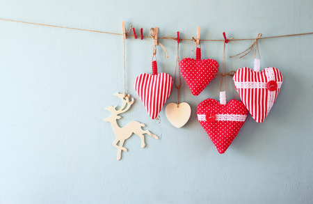 christmas lights background: christmas image of fabric red hearts and tree. wooden reindeer and garland lights, hanging on rope in front of blue wooden background. retro filtered
