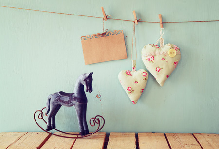 wooden toy: vintage rocking horse next to fabric hearts and empty card for adding text hanging on the rope on wooden floor. retro filtered image
