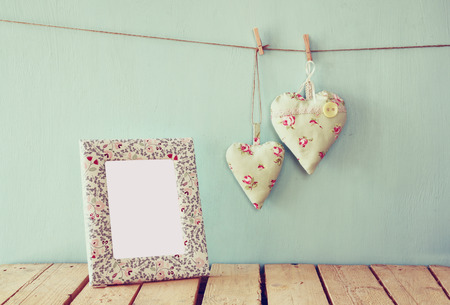 xmas crafts: image of blank frame and hanging fabric hearts on rope in front of wooden background. retro filtered image Stock Photo