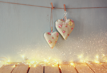 art vintage: low key image of christmas image of fabric hearts hanging on rope in front of wooden background. retro filtered with glitter overlay