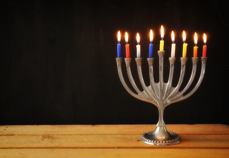 candles: Image of jewish holiday Hanukkah background with menorah traditional candelabra Burning candles over black background