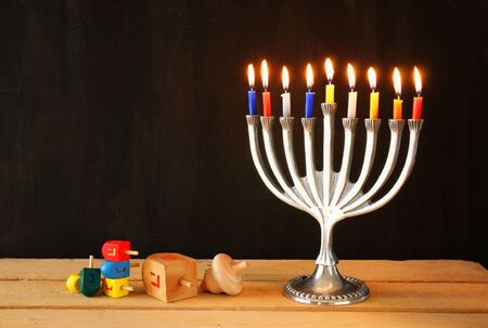 hanukah: low key image of jewish holiday Hanukkah with menorah traditional Candelabra and wooden dreidels spinning top.
