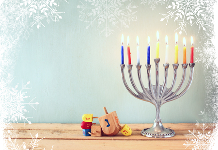 dreidels: image of jewish holiday Hanukkah with menorah traditional Candelabra and wooden dreidels spinning top. glitter and snowflakes overlay