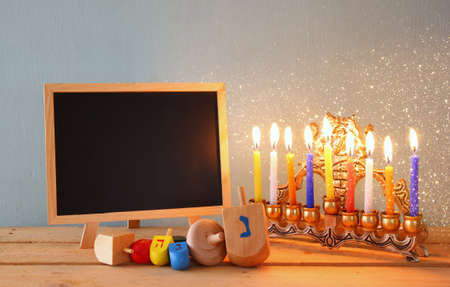 hanukiah: low key image of jewish holiday Hanukkah with menorah traditional Candelabra and wooden chalkboard , room for text