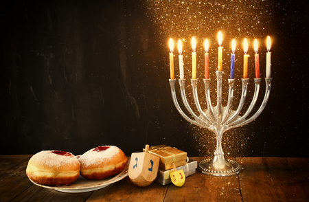 jewish: image of jewish holiday Hanukkah with menorah traditional Candelabra, donuts and wooden dreidels spinning top