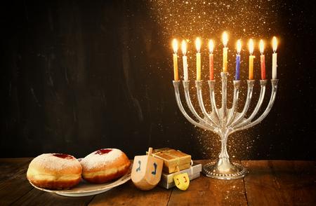 simbolos religiosos: imagen del día de fiesta judío Hanukkah con candelabros menorah tradicional, donas y dreidels de madera peonza Foto de archivo
