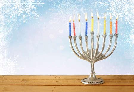 judaic: image of jewish holiday Hanukkah with menorah traditional Candelabra. glitter and snowflakes overlay Stock Photo