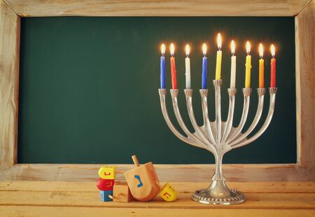 hanukiah: low key image of jewish holiday Hanukkah with menorah traditional Candelabra and wooden dreidels spinning top with chalkboard background, room for text Stock Photo