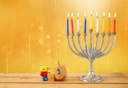 jewish background: image of jewish holiday Hanukkah with menorah traditional Candelabra, and wooden dreidels spinning top