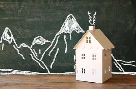 photo of toy house in front of chalkboard with winter concept mountain drawings