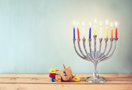 low key image of jewish holiday Hanukkah with menorah traditional Candelabra and wooden dreidels spinning top