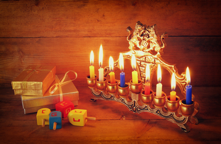 jewish background: low key image of jewish holiday Hanukkah with menorah traditional Candelabra and wooden dreidels spinning top