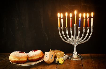 jewish background: image of jewish holiday Hanukkah with menorah traditional Candelabra, donuts and wooden dreidels spinning top