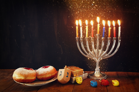image of jewish holiday Hanukkah with menorah traditional Candelabra, donuts and wooden dreidels spinning top
