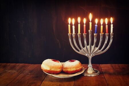 jewish background: image of jewish holiday Hanukkah with menorah traditional Candelabra, donuts