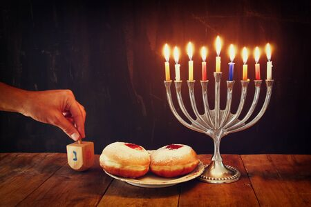 jewish culture: image of jewish holiday Hanukkah with menorah traditional Candelabra, donuts and wooden dreidels spinning top