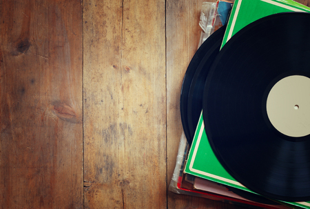 records stack with record on top over wooden table. vintage filtered Foto de archivo