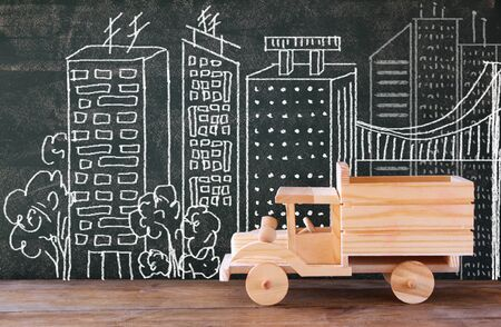 wooden toy: photo of wooden toy truck in front of chaklboard with city illustration.