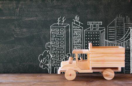 juguetes de madera: foto de camión de juguete de madera delante de chaklboard con la ilustración de la ciudad. Foto de archivo