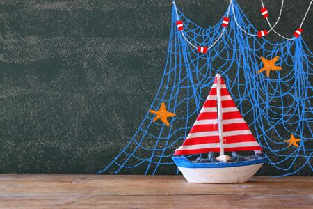 fishnet: photo of wooden sailing boat in front of chaklboard with nautical illustrations. Stock Photo