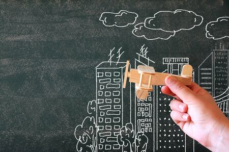 wooden toy: close up photo of womans hand holding wooden toy airplane against chalkboard with city illustration.success and inspiration concept