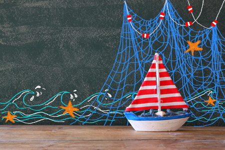 photo of wooden sailing boat in front of chaklboard with nautical illustrations. Stock Photo