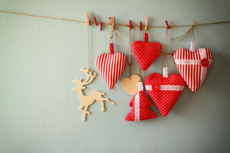 wooden reindeer: christmas image of fabric red hearts and tree, wooden reindeer, hanging on rope in front of blue wooden background. retro filtered Stock Photo