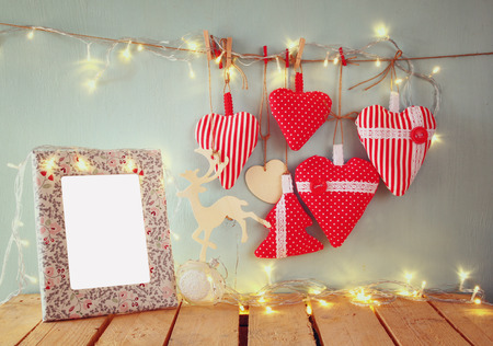 photography: christmas image of fabric red hearts and blank frame, garland lights, hanging on rope in front of blue wooden background. retro filtered. Template ready to put photography Stock Photo