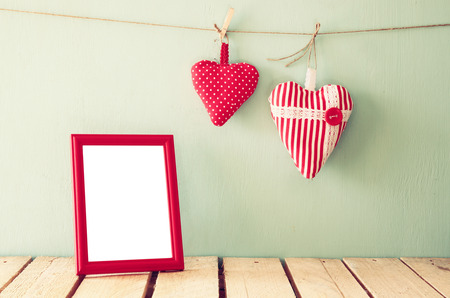 albums: image of red fabric hearts hanging on rope and blank frame in front of wooden background. retro filtered