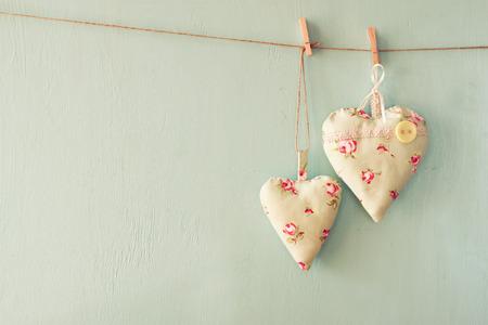 imagen: imagen de corazones de tela colgando de la cuerda delante de fondo de madera azul. retro filtrada