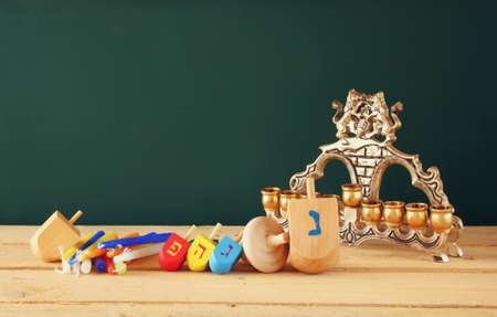dreidels: low key image of jewish holiday Hanukkah with menorah traditional Candelabra and wooden dreidels spinning top with chalkboard background, room for text Stock Photo
