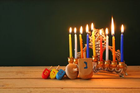 chanukiah: low key image of jewish holiday Hanukkah with menorah traditional Candelabra and wooden dreidels spinning top with chalkboard background, room for text Stock Photo
